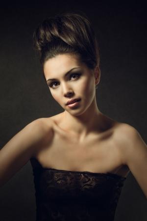 fashion shoot: Beautiful woman portrait over dark vintage background Stock Photo