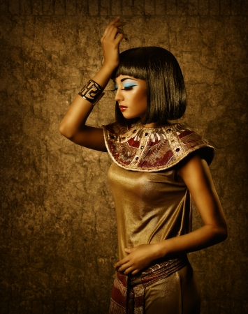 Beautiful egyptian woman bronze portrait over grunge dark gold background photo