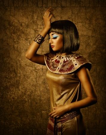 Prachtige Egyptische vrouw bronzen portret over grunge donkere gouden achtergrond