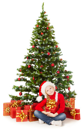 Christmas child in Santa hat sitting under fir tree, holding  gift box photo