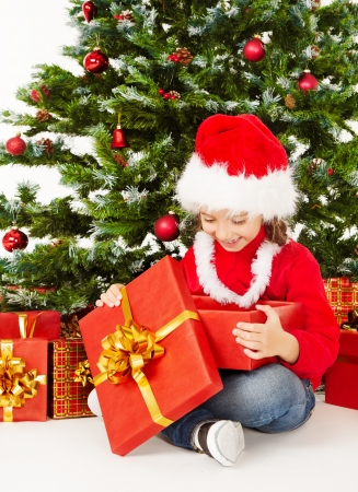Christmas child in Santa hat sitting under fir tree, holding open gift box photo