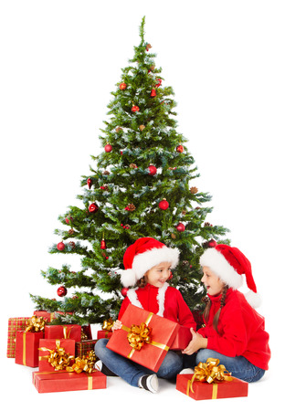 Christmas kids in Santa hat sitting under fir tree, holding open gift box photo
