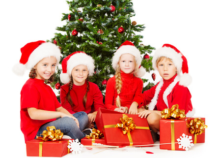 Christmas kids in Santa hat  with presents sitting under fir tree. White background. photo