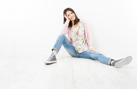 Active young woman teenager in jeans and sneakers sitting on floor over white background photo