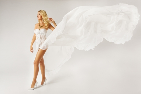 Beautiful woman blonde in white dress with flying fabric   photo
