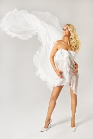 Beautiful woman blonde in white dress with flying dynamic fabric walking   photo