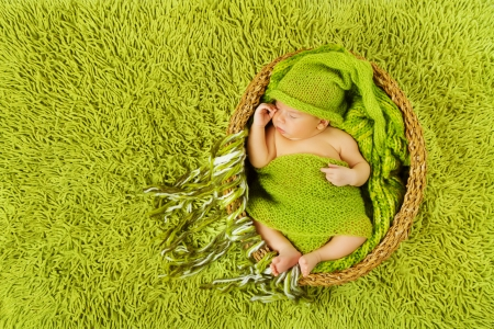 Baby newborn sleeping in woolen hat inside basket over green carpet background  photo