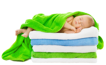 Baby newborn sleeping wrapped in bath towels over white background photo