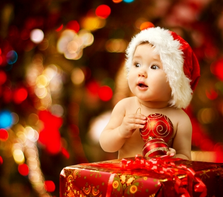 xmas baby: Christmas baby in santa hat holding red ball near present gift box  Stock Photo