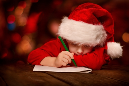 writing    letter: Christmas child writing letter in red Santa hat