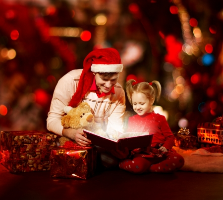 Christmas family reading book. Father and child opening magic fairy tale over red background. Stock Photo - 23572462