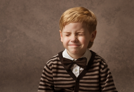 Child happy portrait with closed eyes. Boy in brown retro bow tie waiting surprise  photo