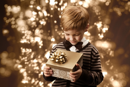 Child holding gift box. Boy in vintage style smart casual clothing, brown colors. photo