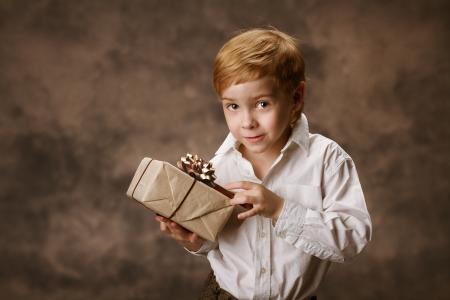 Child holding gift box. Vintage style. photo
