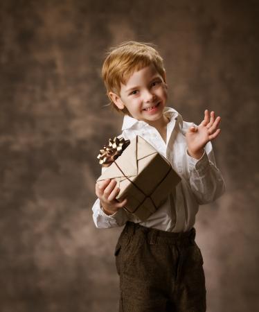 Child holding present gift box, brown vintage style birthday. photo