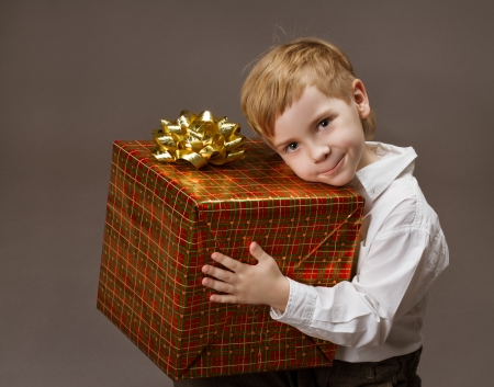 Child holding gift box. Boy with present  photo