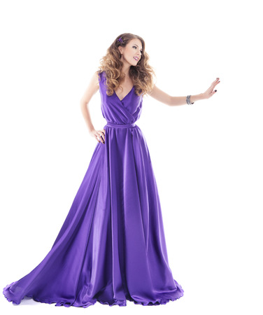 Woman showing advertisement in purple silk dress isolated over white background
