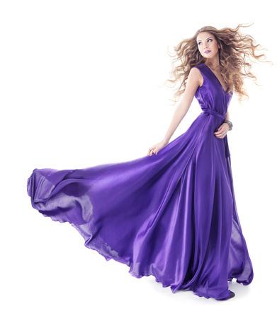 vestido de noche: Mujer en vestido púrpura de seda ondeando pie sobre fondo blanco aisladas