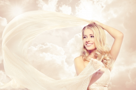 Happy woman, beautiful blonde carefree dancing with flying fabric over sunshine sky photo