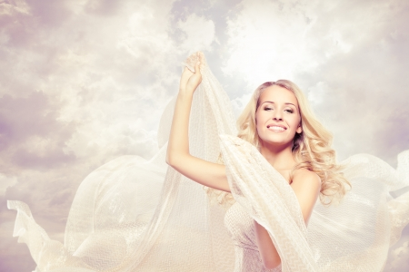 Happy woman, beautiful blonde carefree dancing with flying fabric photo