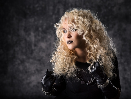Woman blonde curly hair, beauty portrait in black rock style over dark background