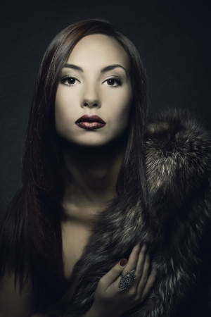 Woman beauty portrait in luxury fur coat. Dark background.  photo
