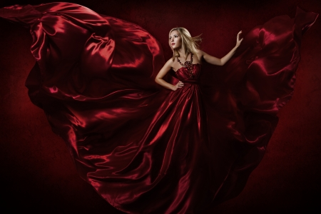 Woman in red waving dress dancing with flying fabric  photo