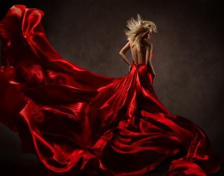 Vrouw in rode golvende kleding met vliegende stof. Terug zijaanzicht Stockfoto
