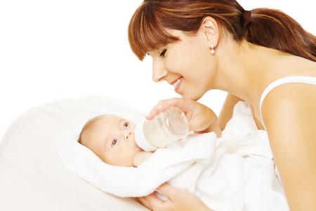 teteros: La alimentación del bebé. Recién nacido de comer leche de la botella en la mano de la madre, backgtound blanco