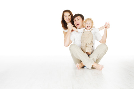 sideway: happy family, smiling father mother and laughting baby sitting over white background  Stock Photo