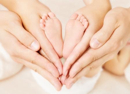 ni�os sosteniendo un cartel: Pies de reci�n nacido a los padres sosteniendo en las manos. Amor simbol como muestra del coraz�n. Foto de archivo
