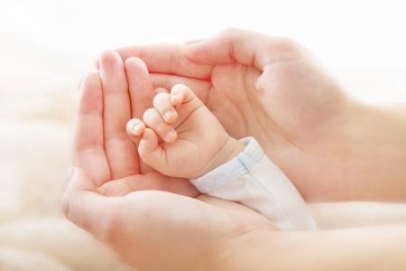 Nyfött barn hand i moder händer. Hjälp och stöd koncept, närbild.