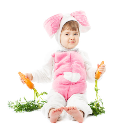 animal masks: baby in easter bunny costume holding fresh carrot, kid girl in  rabbit hare suit sitting over white background Stock Photo