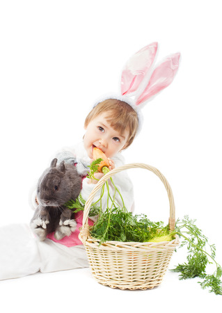 baby in easter bunny costume eating fresh carrot, kid girl holding hare rabbit over white background photo