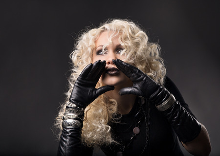 expressive face: Woman shouting with hands around mouth, loud talking speaking, blonde curly hair in black gloves, hands to mouth over gray background