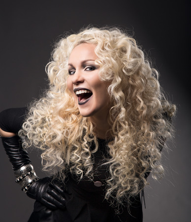 woman blonde curly hairs, surprised with open mouth black lips, beautiful fashion portrait over gray background photo