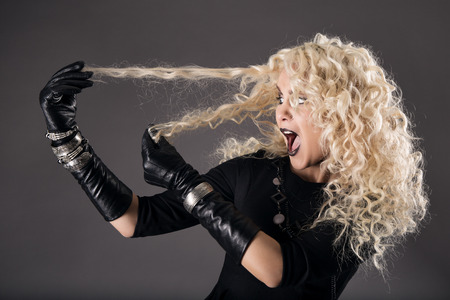 leather glove: curly hairstyle blonde in black, woman hairs loss, coloring problem, beautiful girl holding hairs and surprised, over gray background