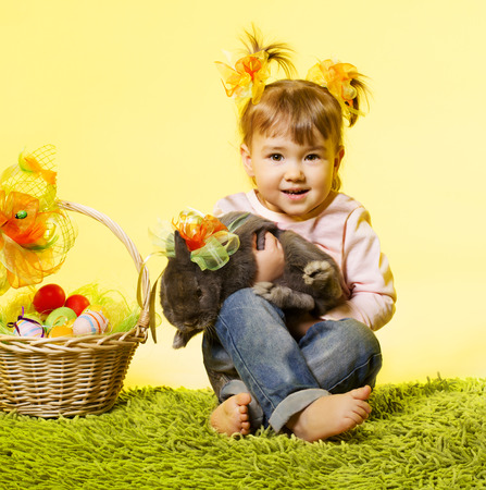 Easter little girl, kid holding bunny rabbit basket eggs over yellow background photo