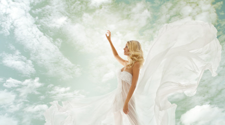 woman blonde in fluttering white dress with flying fabric, beautiful girl showing advertise on sky photo