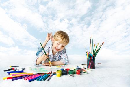 Niño pintando con pincel de color utilizando una gran cantidad de herramientas de dibujo