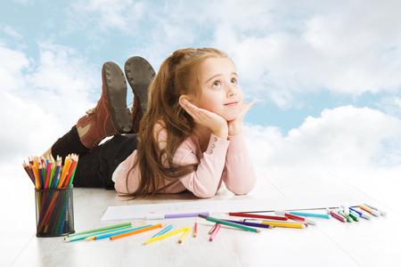 pozitivní: Dívka snění, hledá pro kreslení nápad přes modrou zatažené obloze