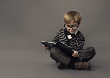 boy book: Boy in glasses reading book Stock Photo