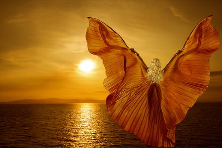 Mujer con alas de mariposa que volaba sobre el mar de fantasía puesta de sol, la relajación meditación concepto