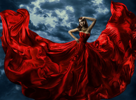 Woman in red evening dress, waving gown with flying long fabric over artistic sky background