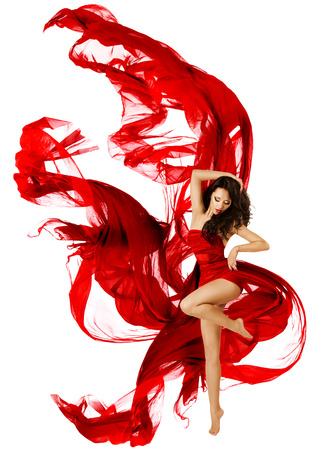 Woman dancing in red dress, fashion model dance whit waving fluttering fabric over white background photo