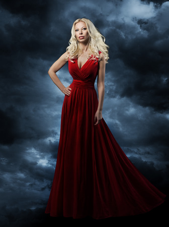 Woman in red dress, long hair blonde in fashion evening gown over sky background, hand on hip photo