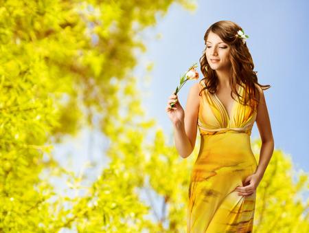 vrouw ruikende bloemen, voorjaar portret van mooie meisje in gele jurk Stockfoto