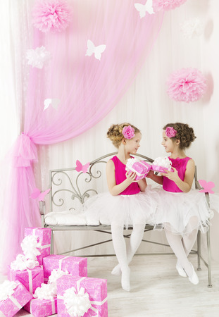 kids birthday party: Girl giving children birthday present to sister. Kids and party gift boxes in pink color