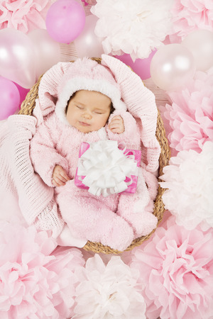 Baby girl with gift sleeping on pink background, newborn and  present  Birthday party invitation card photo