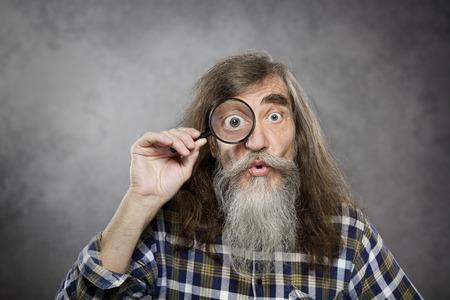 investigacion: Viejo hombre mayor que mira con lupa zoom investigación asombro divertido anciano o pérdida de la visión de ensayo Foto de archivo